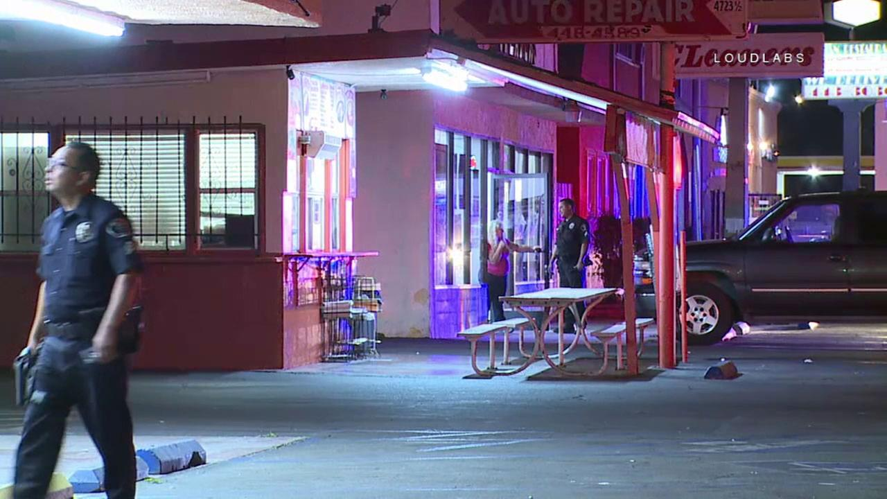 Police say an armed man in a ski mask doused a taco stand employee with a liquid and then shot her in the knee in El Monte Friday night.
