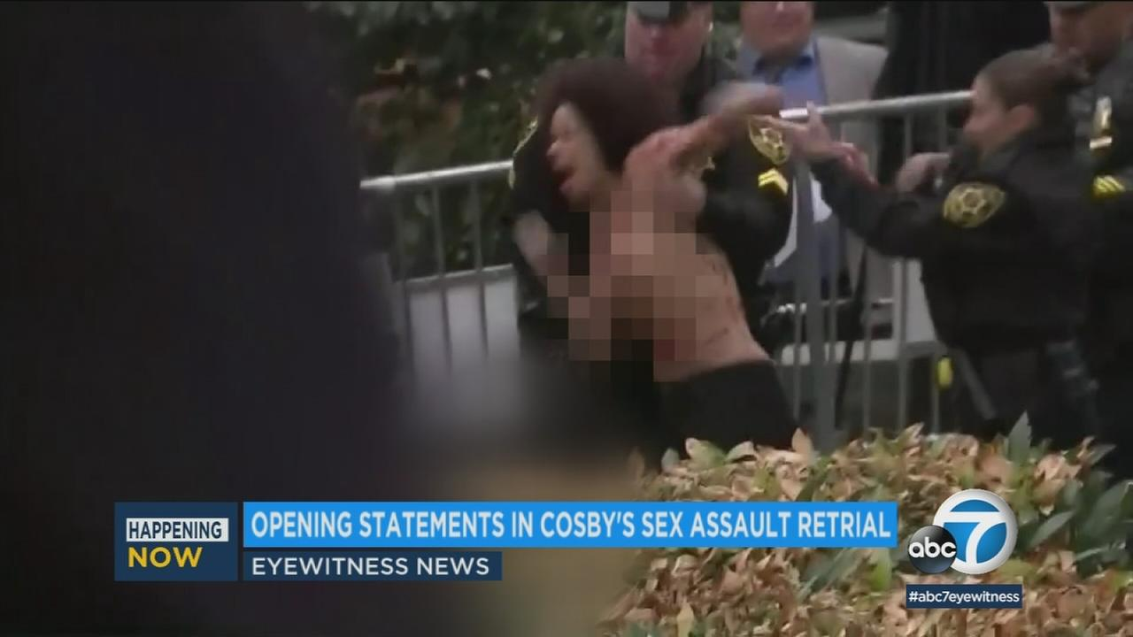 Police take a protester into custody after charging at Bill Cosby as he walked into the courthouse for a sex assault retrial on Monday, April 9, 2018.