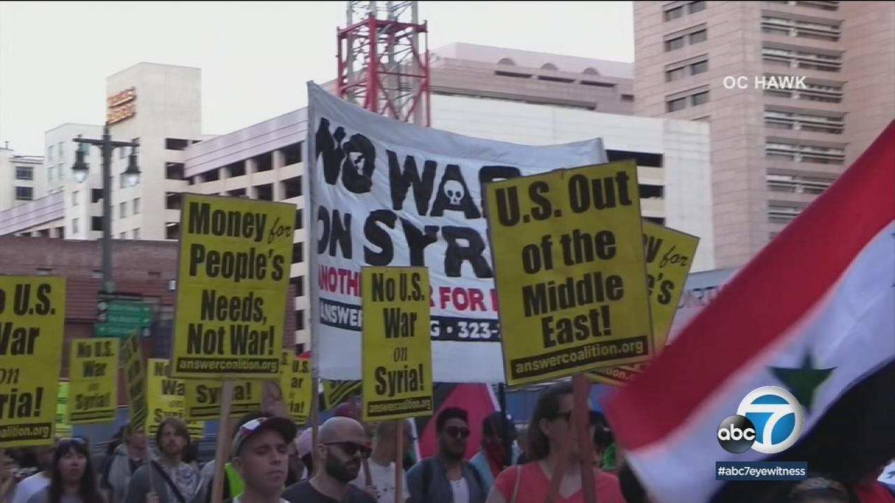 Demonstrators are shown protesting the recent airstrikes in Syria in downtown Los Angeles on Saturday, April 14, 2018.