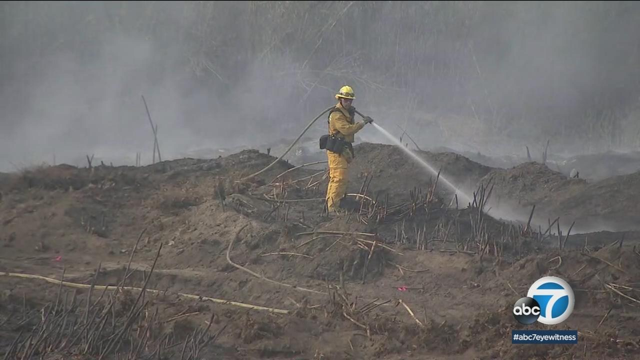A firefighter used water to knock down hot spots in an area where a brush fire broke out in Montebello.