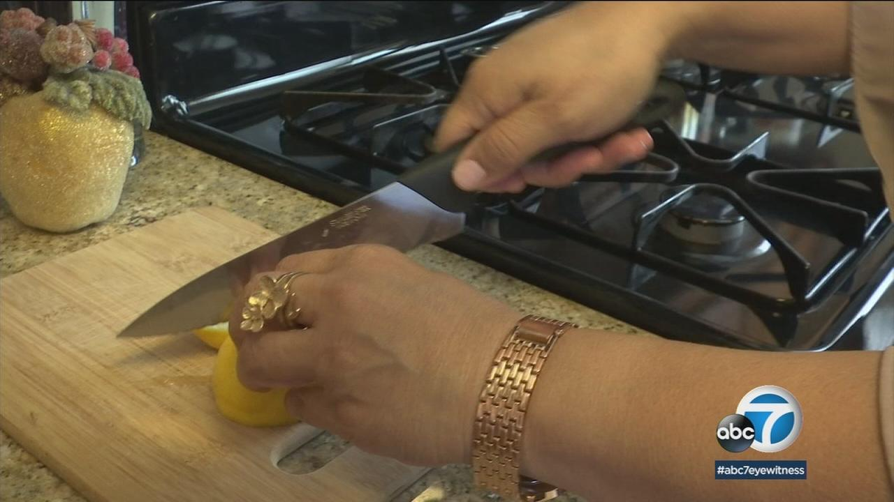 A woman is shown cutting her food in her kitchen.