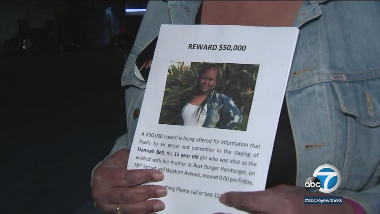 A woman holds flyers with a photo of Hannah Bell, 15, on it in an effort to find the person who shot and killed her.