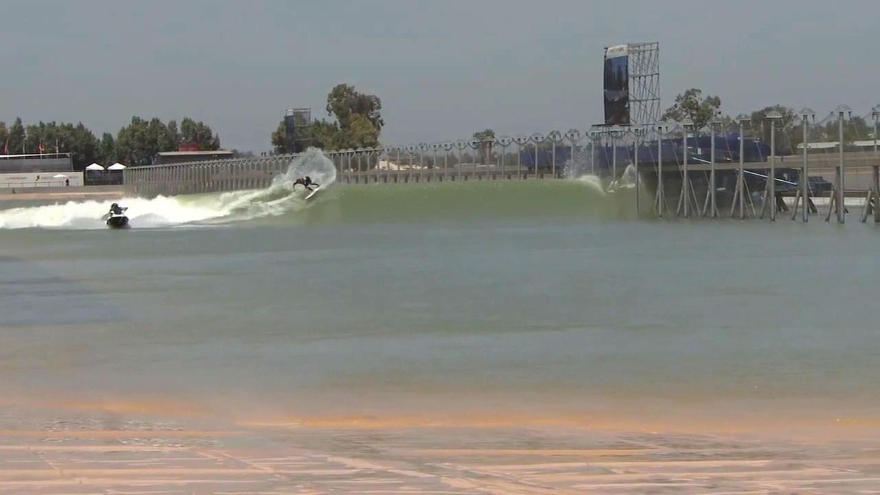 A professional surfer catches a wave created by a hydrofoil at a surf ranch in a man-made lake in Lemoore, California.