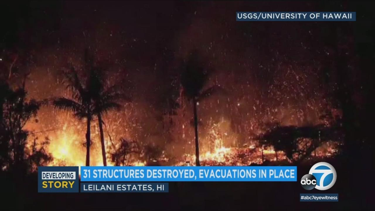 An image shows lava spewing out in the Leilani Estates subdivision.