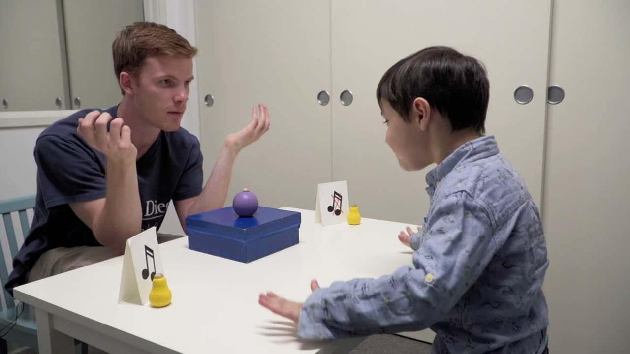 A researcher asks a child a question during a developmental psychology study.