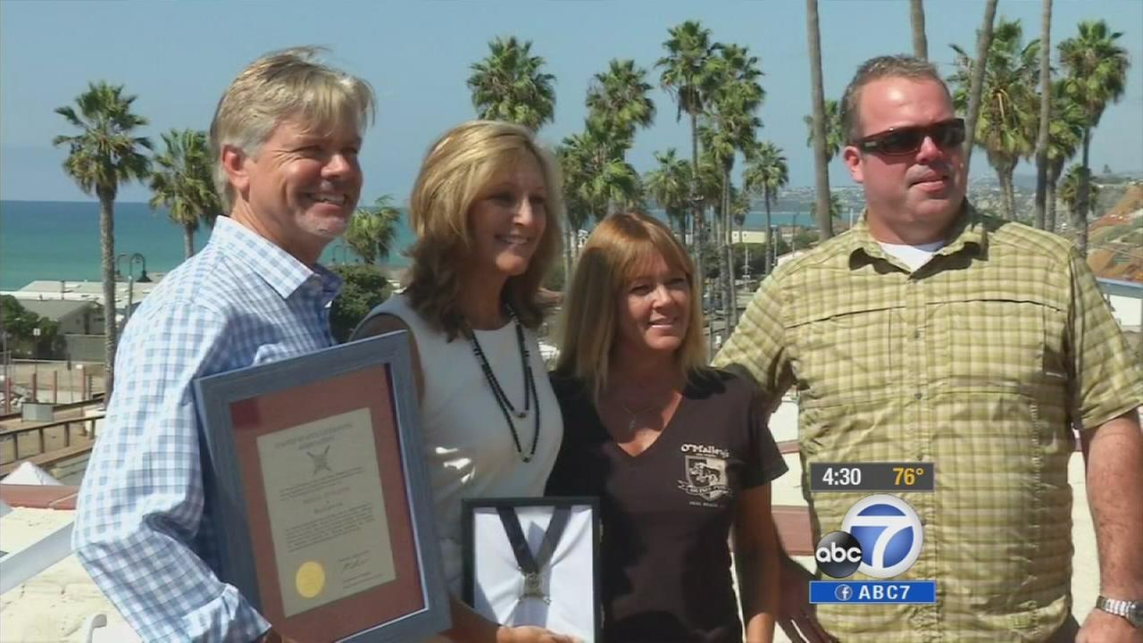 Ben Carlsons parents Chris and Terry (left) accept their sons medal of valor on Thursday, Oct. 9, 2014.