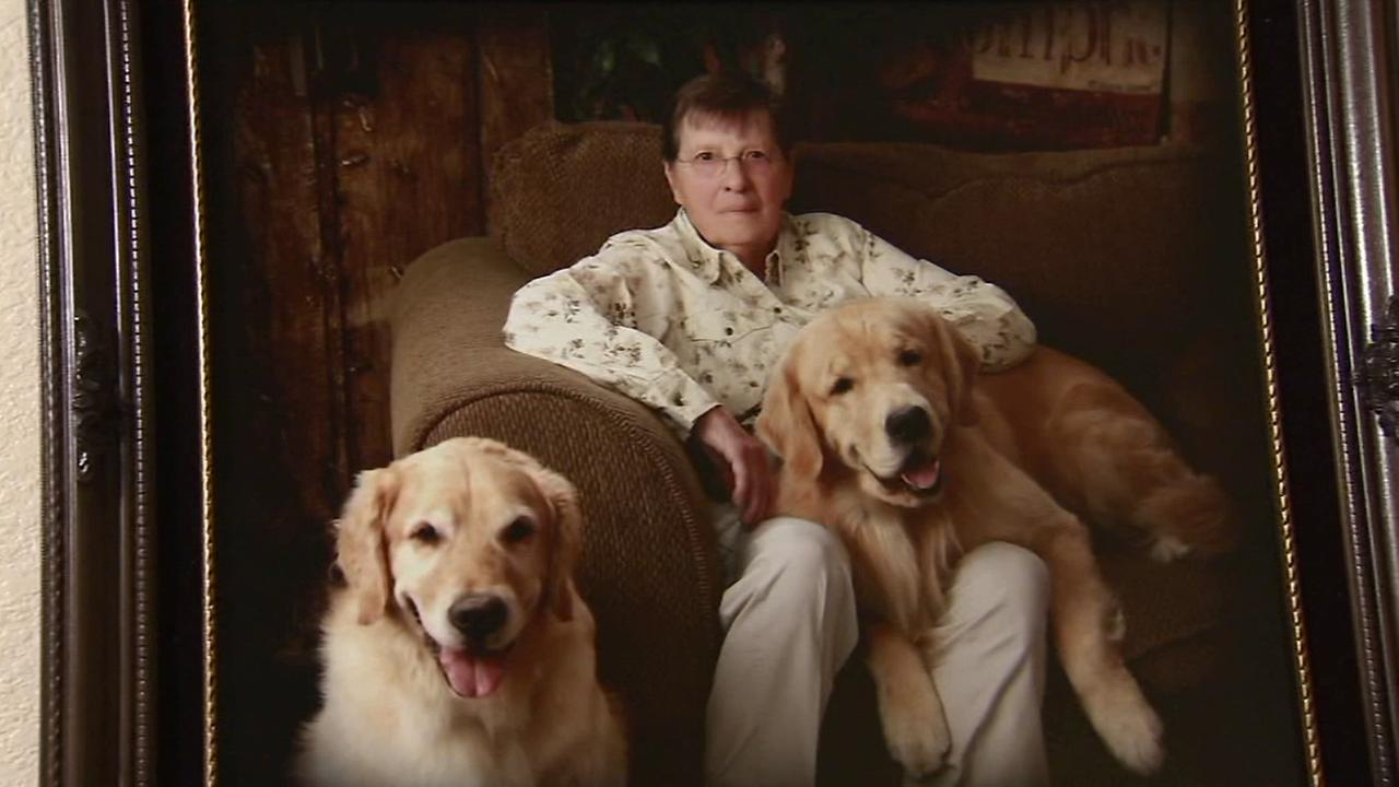 Judy Muhe is seen with her two dogs in a family photo, which hangs in her Palmdale home.