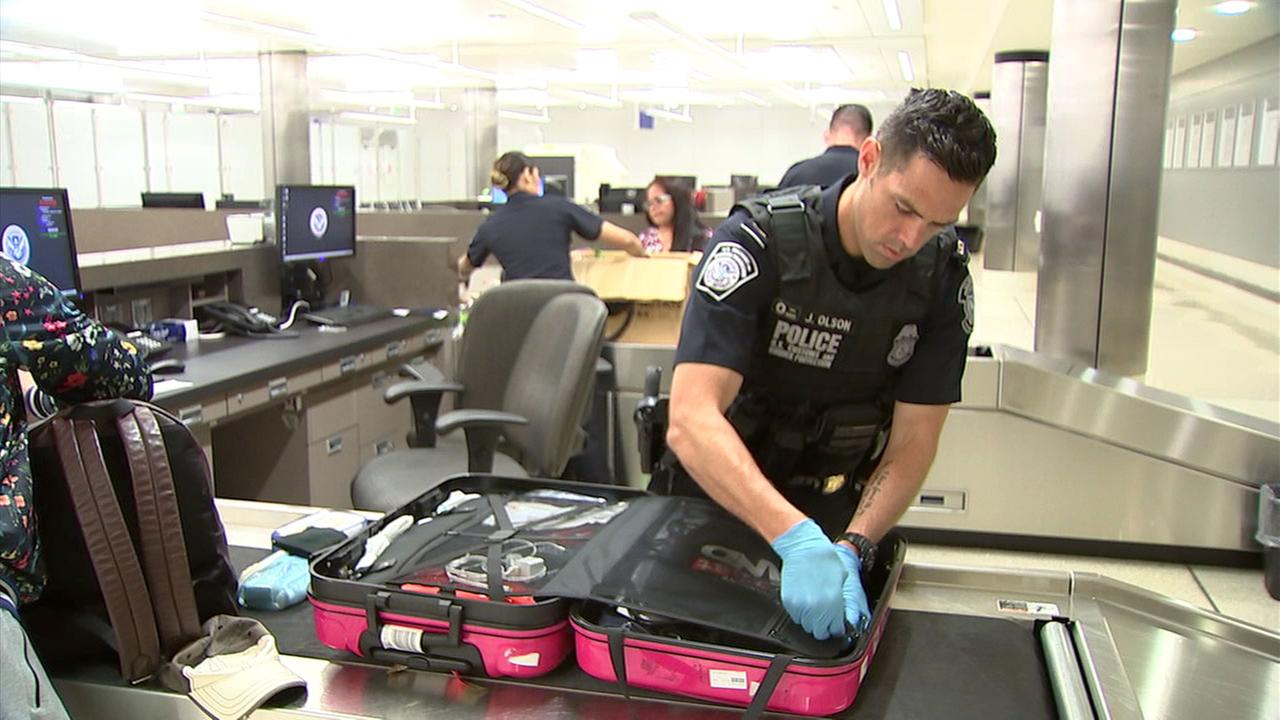 A U.S. Customs and Border Protection agent searches a suitcase at LAX.