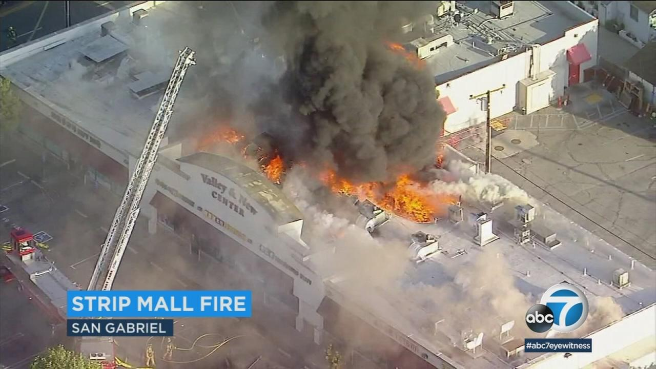 A fire ripped through a strip mall in San Gabriel early Wednesday morning, spewing flames and pillars of thick smoke into the air.