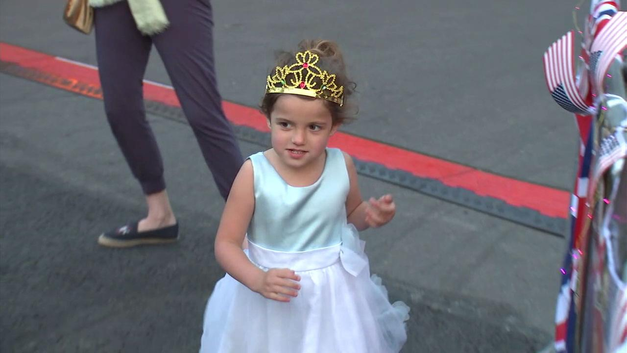 A little girl from Virginia wears a tiara on her head and dons a princess dress as she walks around a London street.