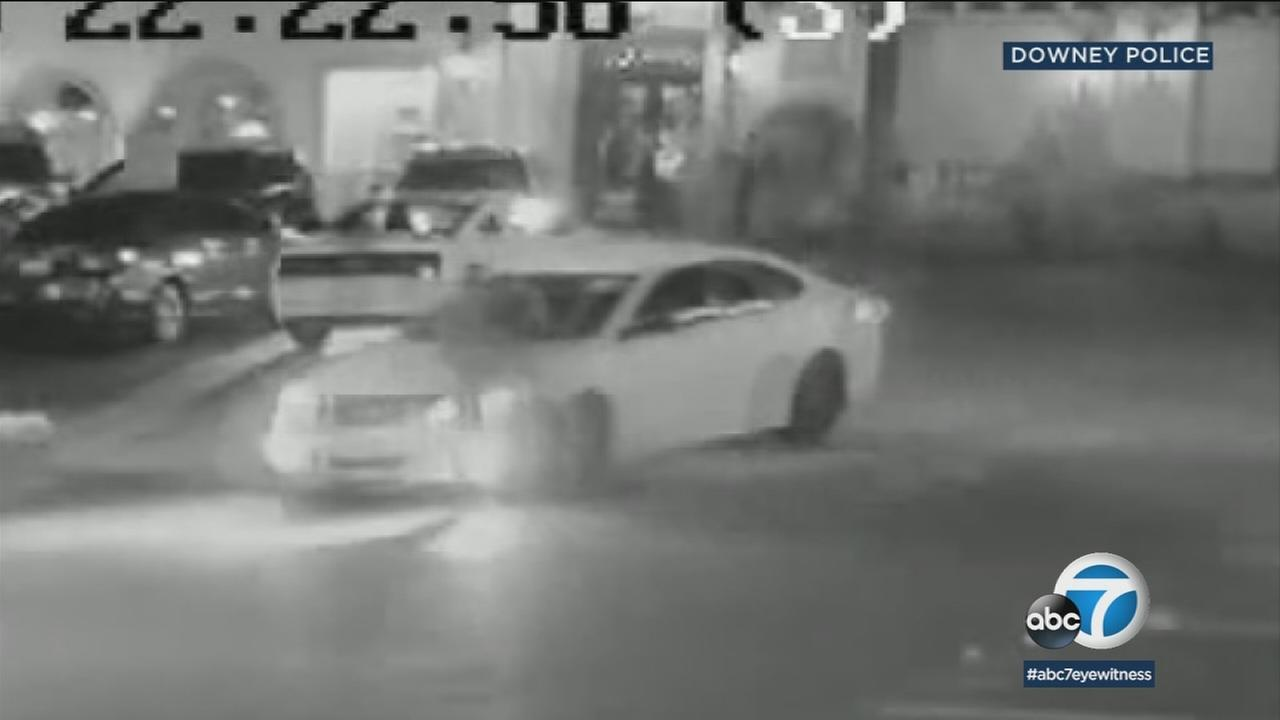 Surveillance video shows a white Nissan Altima that was used in a hit-and-run in Downey that left a security guard in critical condition.