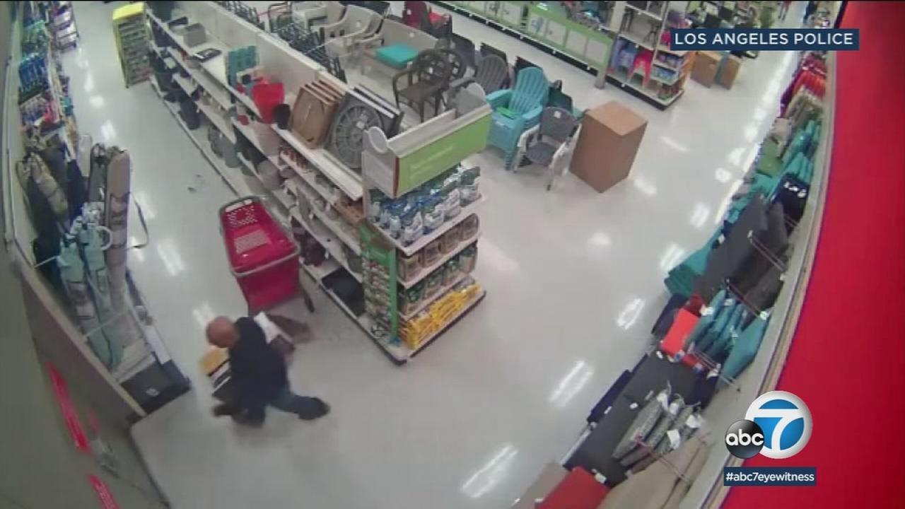 A suspected thief is shown heading to an emergency exit in a Target and walking out with expensive items.
