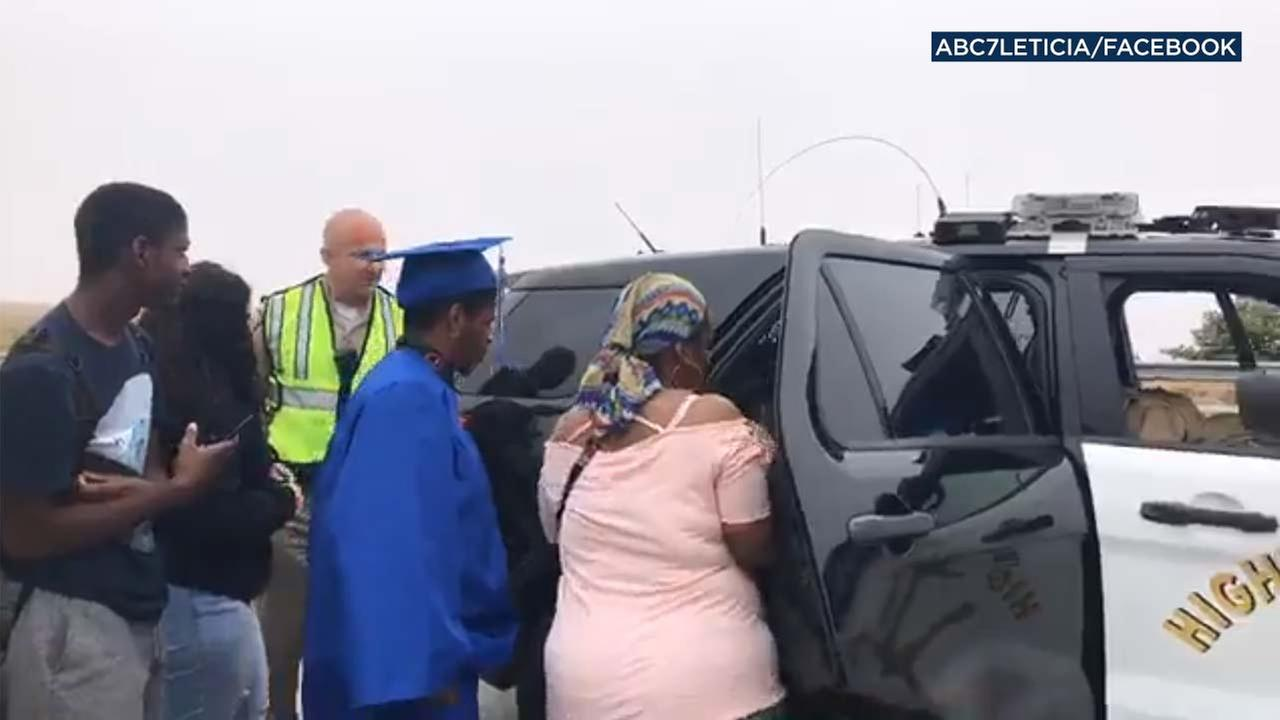 A Mojave High School student dress in a cap and gown gets into a CHP SUV along the Cajon Pass on Wednesday, May 30, 2018.