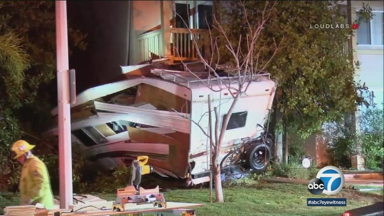 A mangled motorhome is shown sitting outside of a residence in Moreno Valley after the driver of the motorhome crashed into the structure.