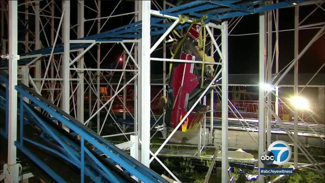A derailed roller coaster car is shown after it caused two people to fall 30 feet and left others dangling above the ground.