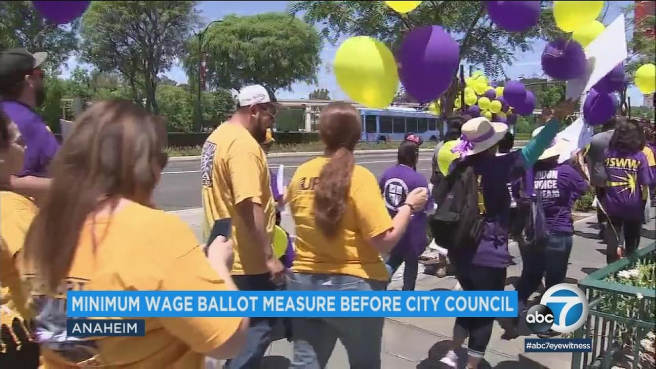 A group of people march in support of higher wages for workers at Disneyland and other resort areas in Anaheim.