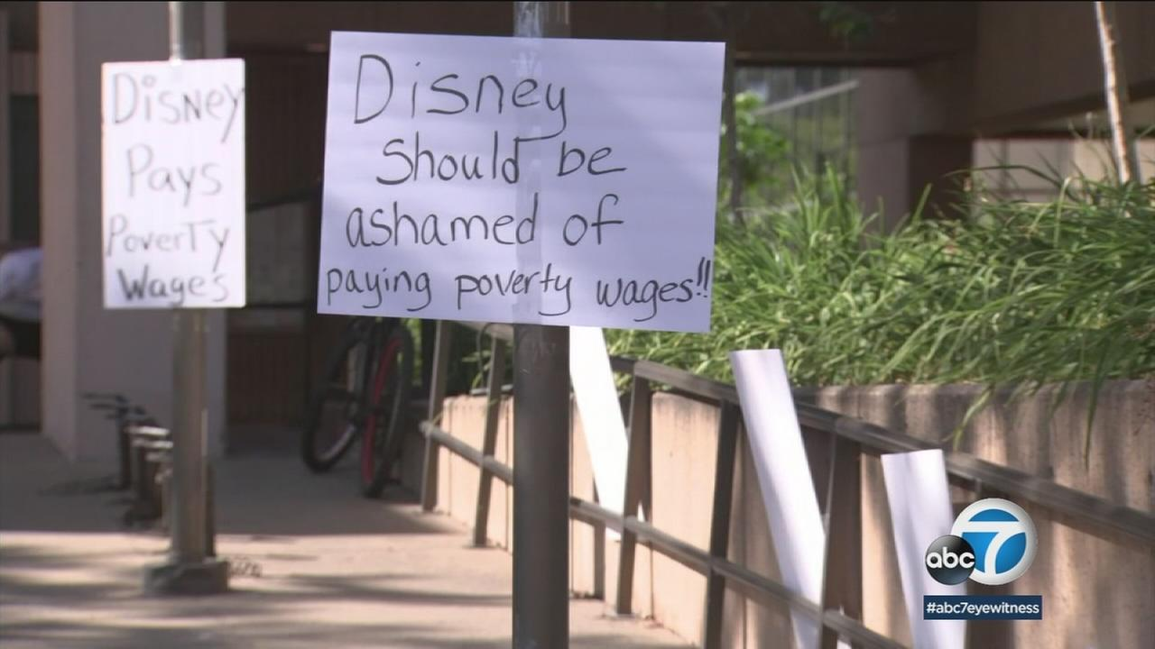 A sign stating Disney should be ashamed of paying poverty wages is shown on a pole as people headed to an Anaheim City Council meeting.