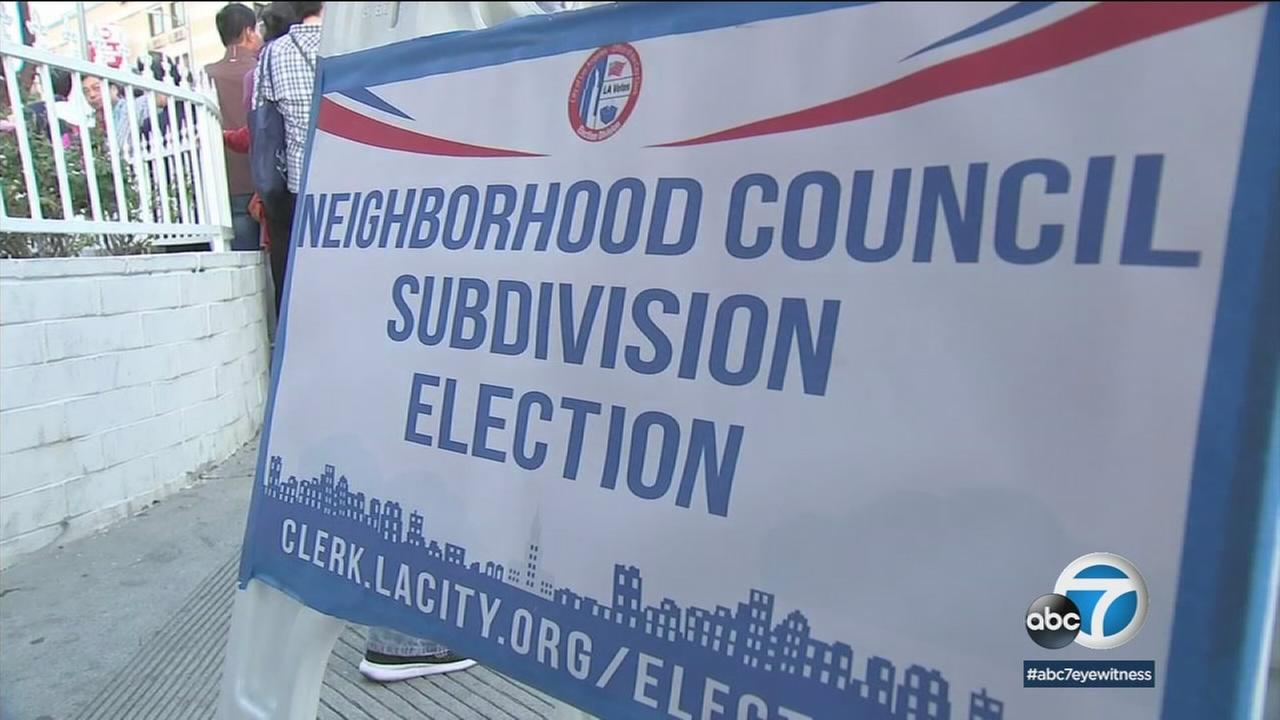 A sign for the neighborhood subdivision committee is shown as people line up to vote on the splitting of Koreatown and Little Bangladesh.