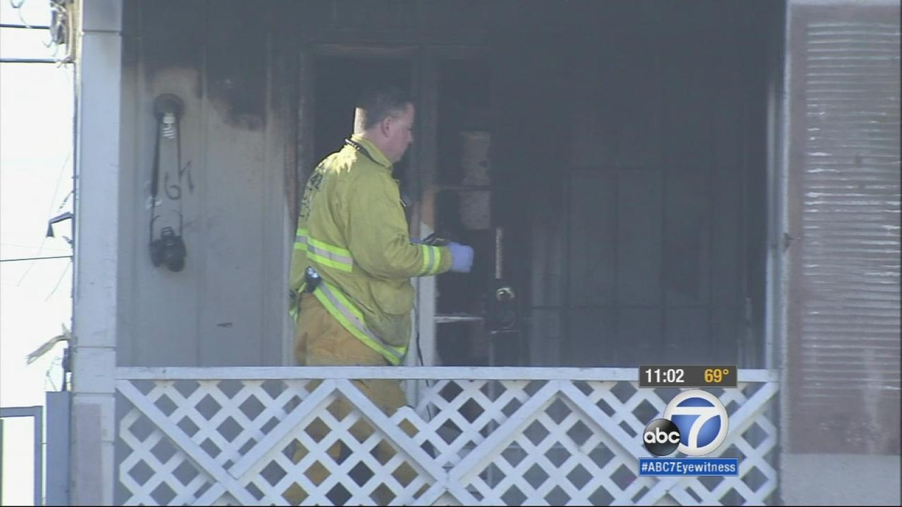 Firefighters investigate a deadly apartment fire in San Bernardino on Thursday, Nov. 20, 2014.
