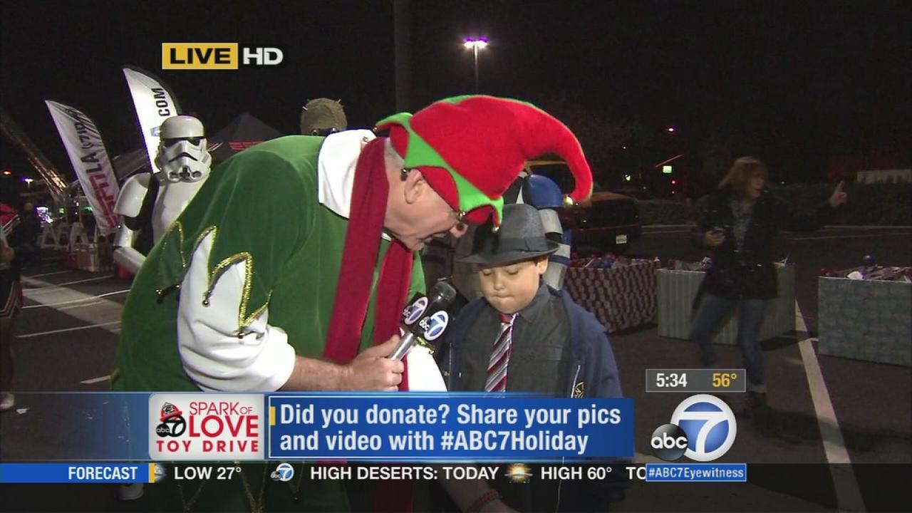 Garth the Elf is seen with 7-year-old Michael at the Stuff-A-Bus event in Cerritos on Friday, Nov. 21, 2014.