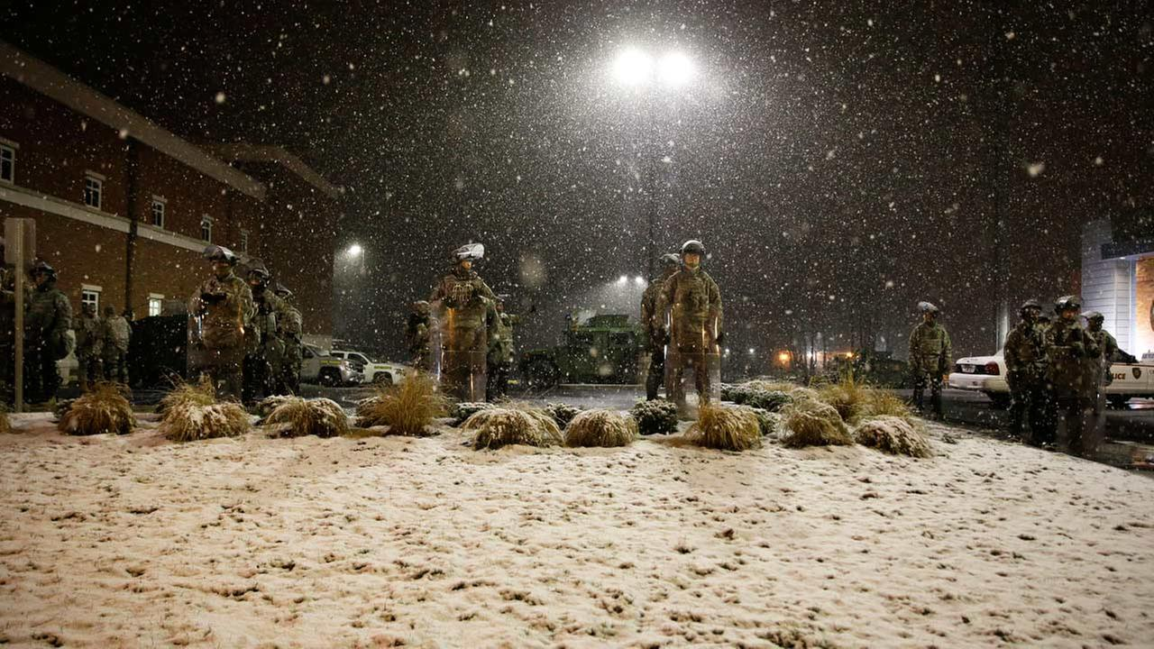 Snow falls as Missouri National Guard stand outside of the Ferguson Police Department Wednesday, Nov. 26, 2014, in Ferguson, Mo.
