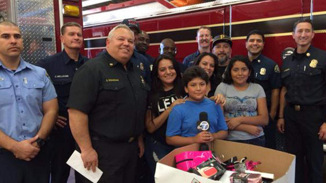 The Mejia family poses for a photo with Monrovia firefighters on Monday, Dec. 22, 2014.