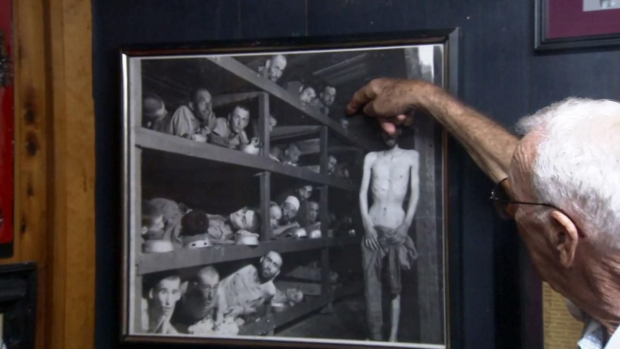 Holocaust survivor Mel Mermelstein points out where he is in a photo of prisoners at Auschwitz.