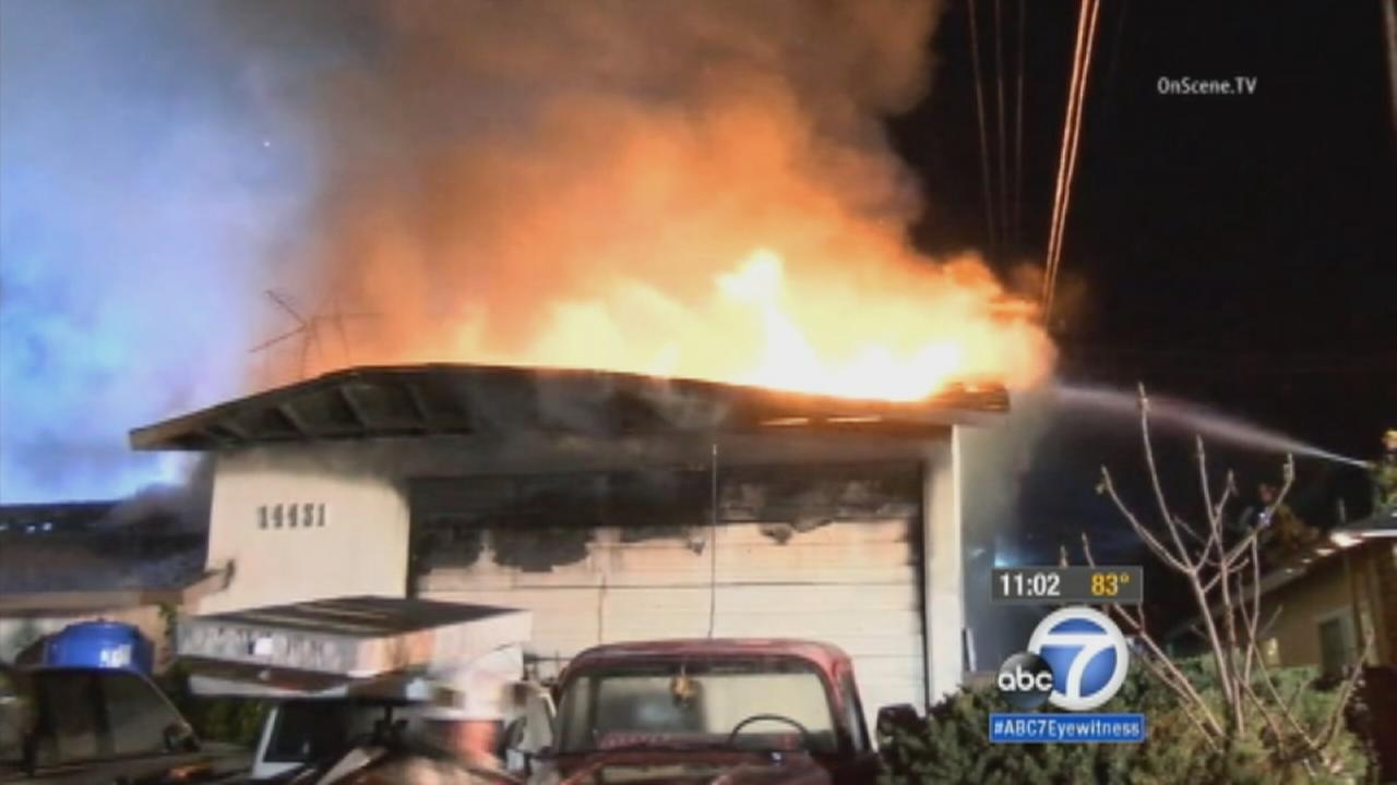 Firefighters battle flames at a home in Garden Grove on Thursday, Feb. 12, 2015.