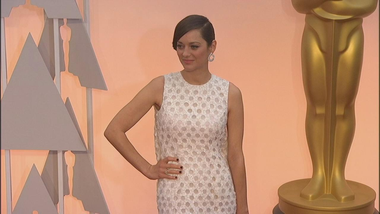 Marion Cotillard, Actress in a Leading Role nominee for Two Days One Night, wars an all white dress on the Oscars red carpet.
