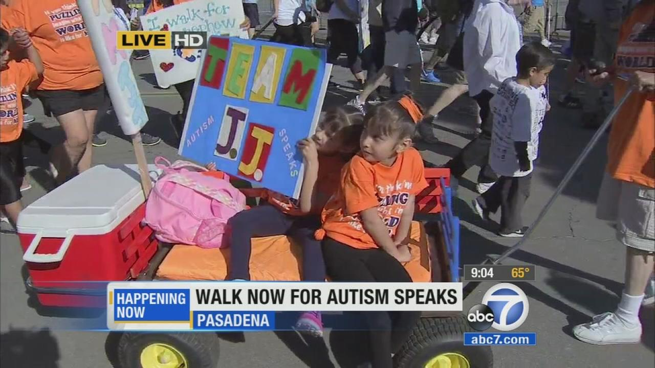 Two young girls sit on a wagon and one holds a sign at the Walk Now for Autism Speaks at the Rose Bowl in Pasadena on Saturday, April 18, 2015.