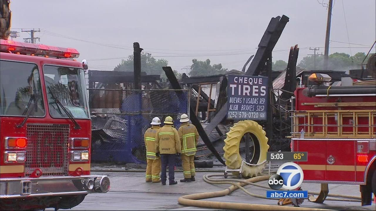 Firefighters work to put out any leftover flames at a tire shop in South El Monte on Saturday, April 25, 2015.