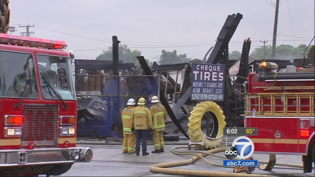 Firefighters investigate the scene of a fire that broke out in a tire shop on Saturday, April 25, 2015.