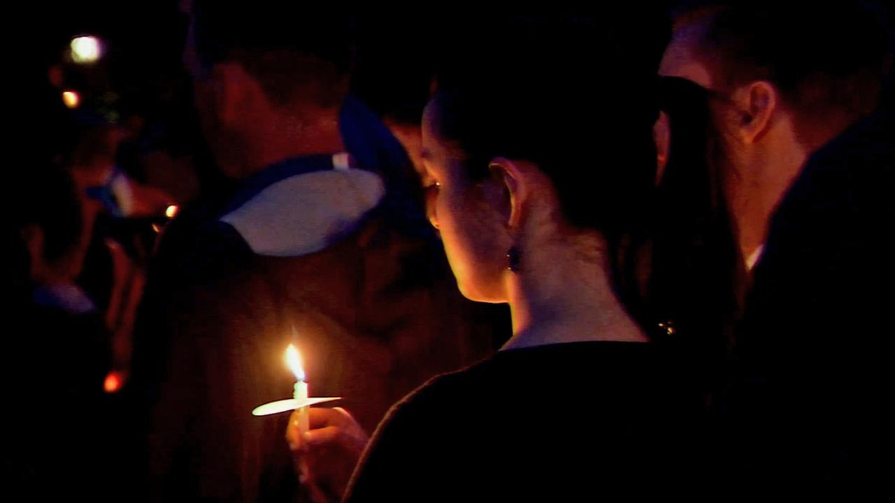 A student hold a candle at a vigil Saturday, May 24, 2014, for the victims in the Isla Vista shootings.