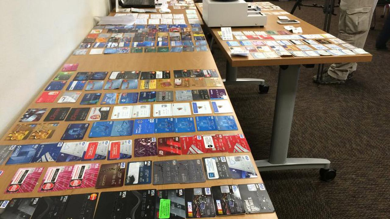 Two people were arrested in Highland Tuesday after authorities pulled over a stolen vehicle and found thousands of stolen credit, identification and social security cards hidden in the trunk.
