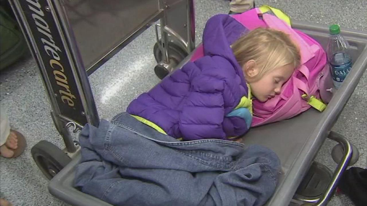 A young girl sleeps at Los Angeles International Airport after the familys flight in Spirit Airlines was canceled on Thursday, Jun 18, 2015.