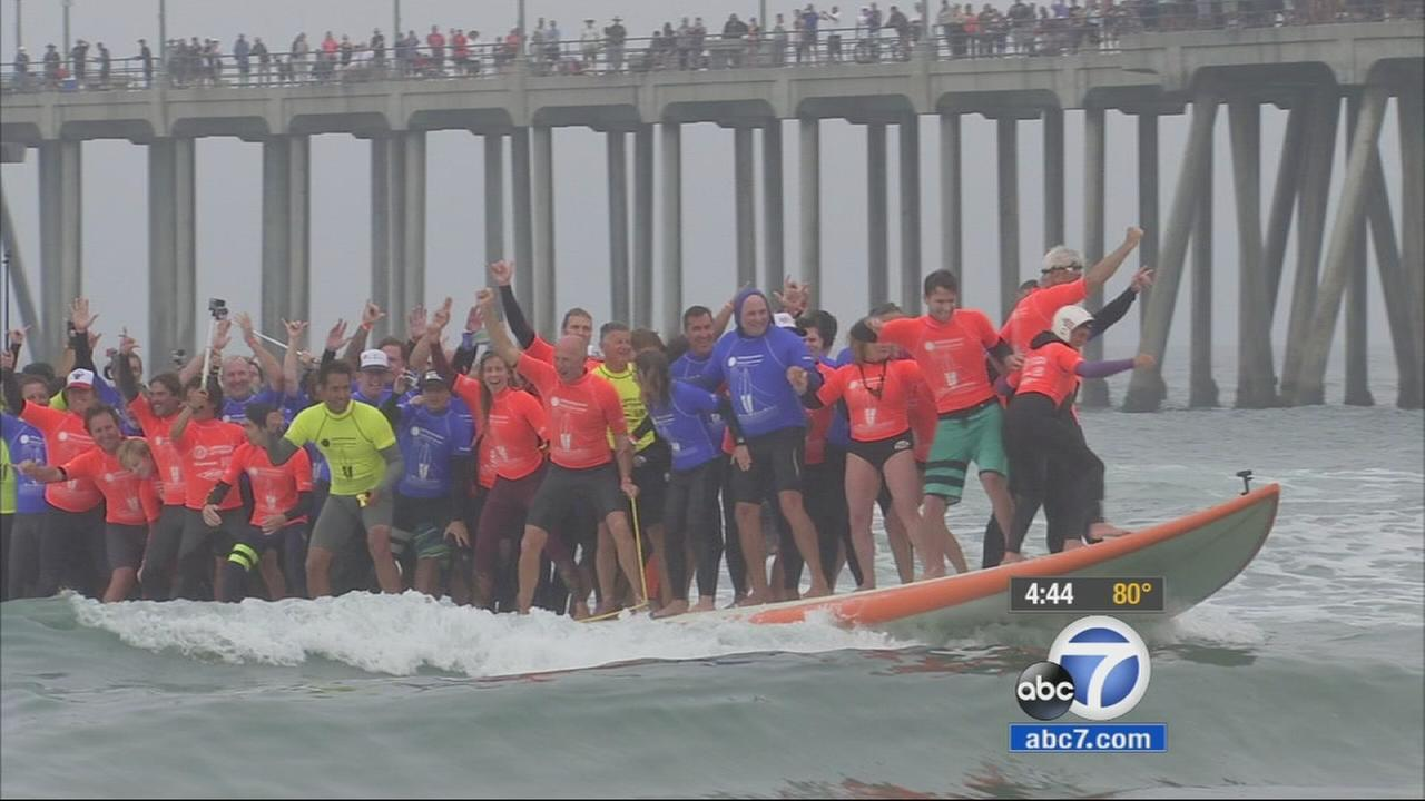 Dozens of surfers in Huntington Beach are attempting to break two world records: the worlds longest surfboard and the number of riders on the board.