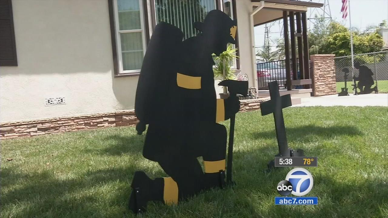 A silhouette of a firefighter, meant as a tribute piece, is put on display on James Krupas yard.