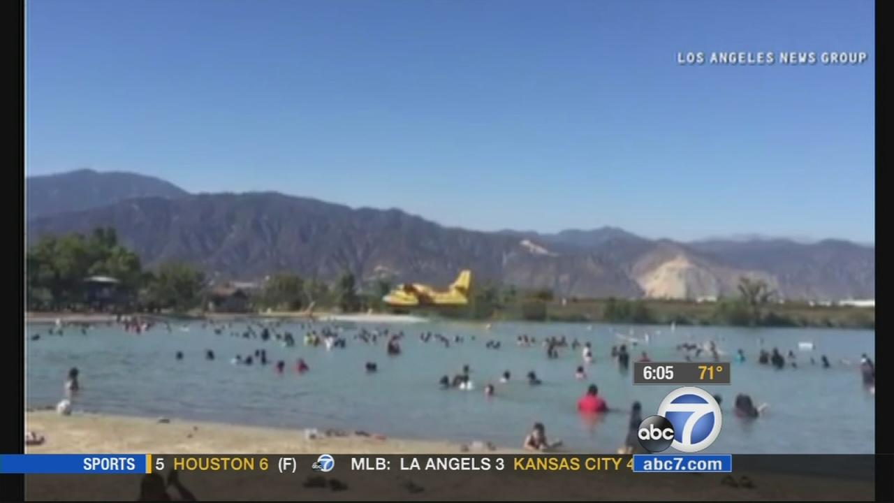 Incredible video caught a Super Scooper firefighting aircraft filling up at the Santa Fe Dam in Irwindale on Sunday, as swimmers looked on.