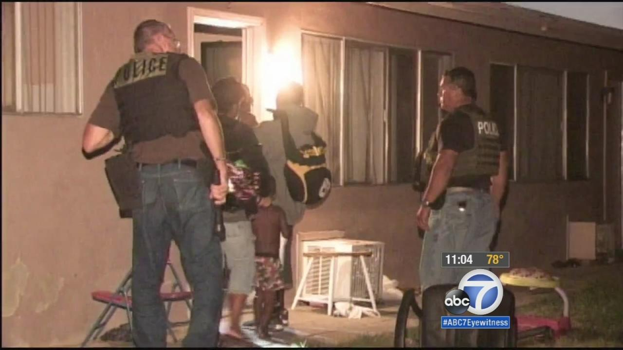 Police are seen escorting residents back into their homes following an evacuation of an apartment building in Moreno Valley.