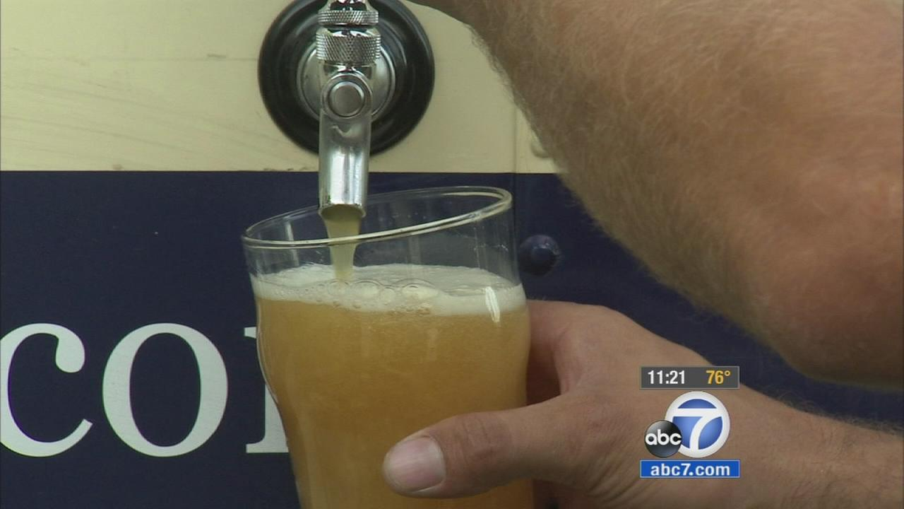 A tap on the outside of a delivery truck for RIIP Beer fills a glass with custom-brewed beer.