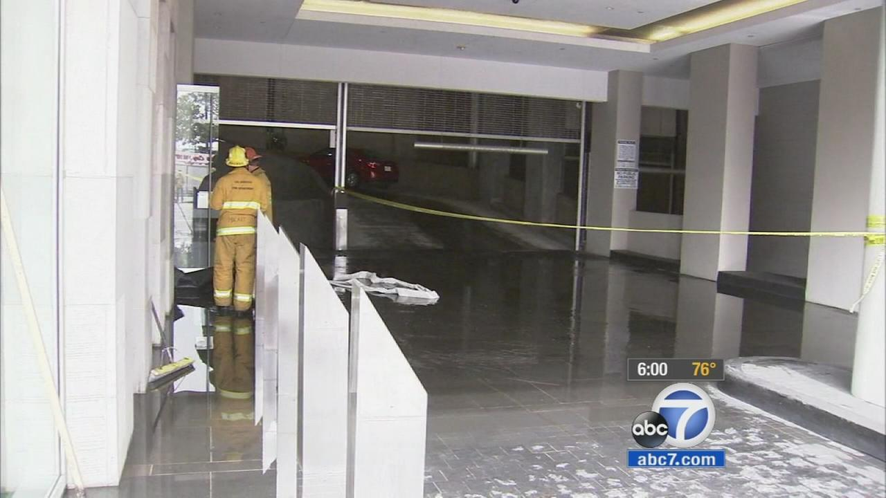 Firefighters work to shut off a water main break from a sprinkler system that flooded 25 floors in a high-rise building in downtown Los Angeles on Monday, Sept. 21, 2015.