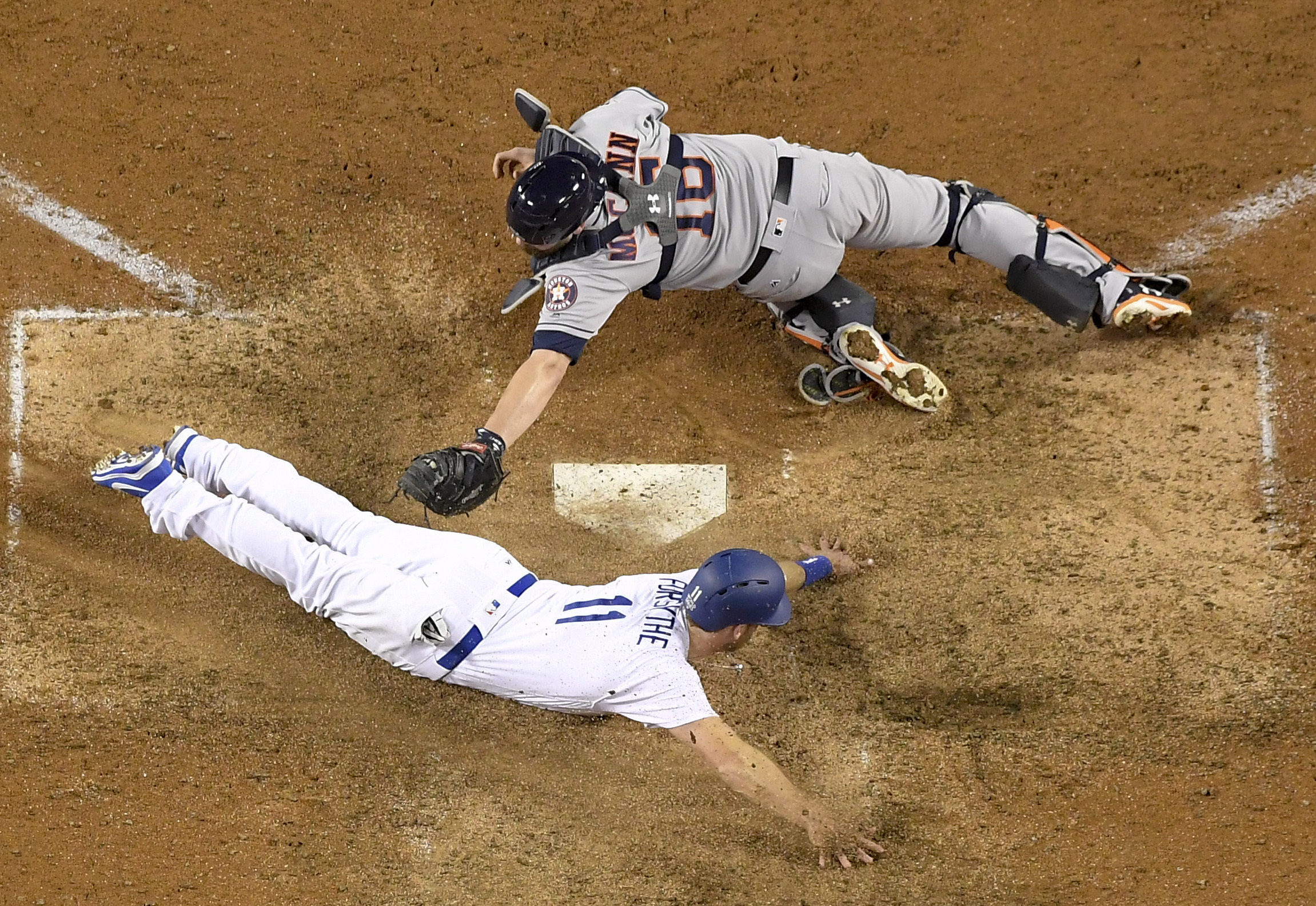 <div class='meta'><div class='origin-logo' data-origin='AP'></div><span class='caption-text' data-credit='(AP Photo/Mark J. Terrill)'>Los Angeles Dodgers' Logan Forsythe, left, scores past Houston Astros catcher Brian McCann on a hit by Enrique Hernandez during the 10th inning of Game 2 of baseball's World Series</span></div>