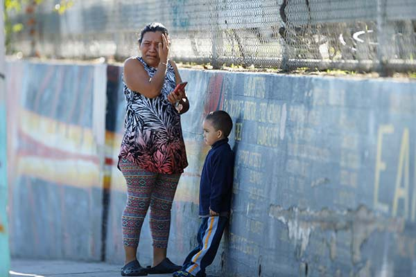 <div class='meta'><div class='origin-logo' data-origin='AP'></div><span class='caption-text' data-credit='Damian Dovarganes'>Elizabeth Acevedo and her son Andres, 3, wait for news of her son, Jose, an 8th grade student at the Belmont High School in Los Angeles Thursday, Feb. 1, 2018.</span></div>