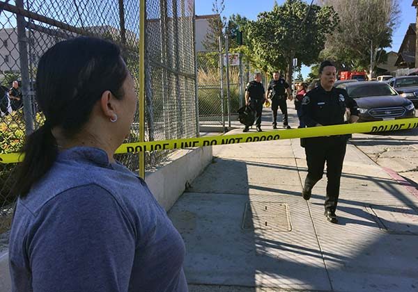<div class='meta'><div class='origin-logo' data-origin='AP'></div><span class='caption-text' data-credit='AP Photo/Amanda Lee Myers'>Gloria Echeverria watches as Los Angeles police officers close off a street where a shooting occurred at a middle school in Los Angeles on Thursday, Feb. 1, 2018.</span></div>