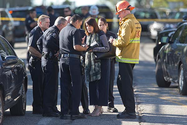 <div class='meta'><div class='origin-logo' data-origin='AP'></div><span class='caption-text' data-credit='AP Photo/Damian Dovarganes'>Los Angeles Fire department's Erik Scott, far right, police officers and school officials gather outside the Belmont High School in Los Angeles Thursday, Feb. 1, 2018.</span></div>