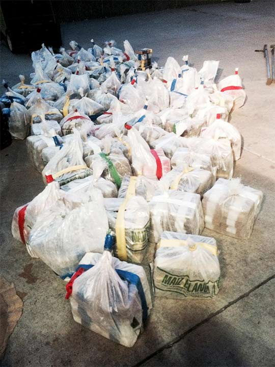 "<div class=""meta image-caption""><div class=""origin-logo origin-image none""><span>none</span></div><span class=""caption-text"">Bundles found inside a large container near the drug tunnel are removed. (United States Department of Justice)</span></div>"