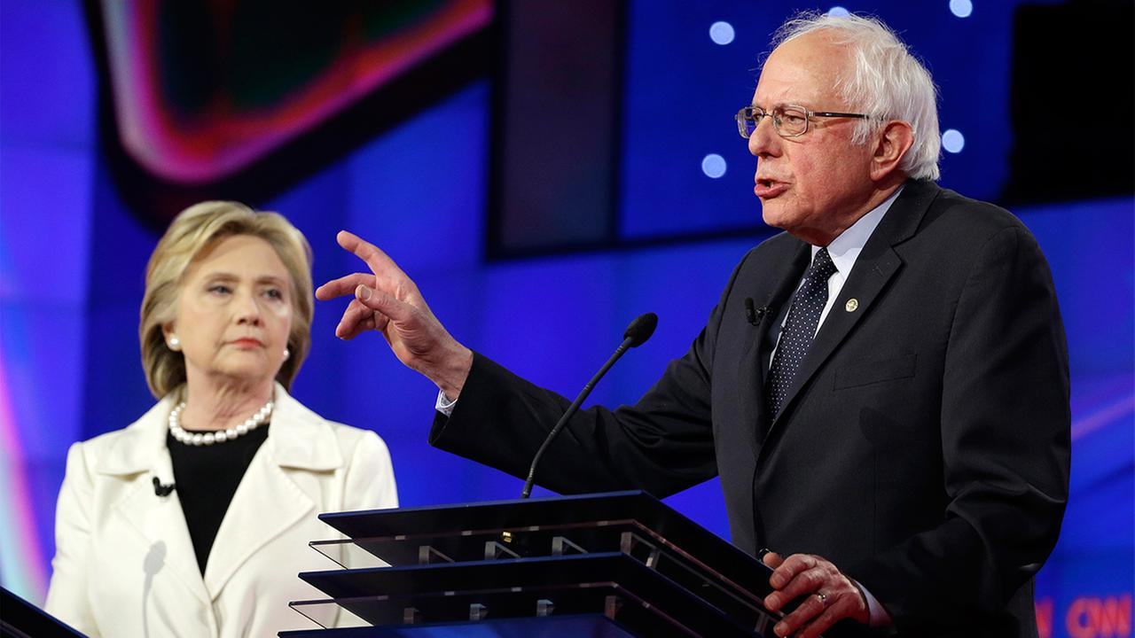Democratic presidential candidate Sen. Bernie Sanders, I-V.t, right, speaks as Hillary Clinton listens during the CNN Democratic Presidential Primary Debate, April 14, 2016.