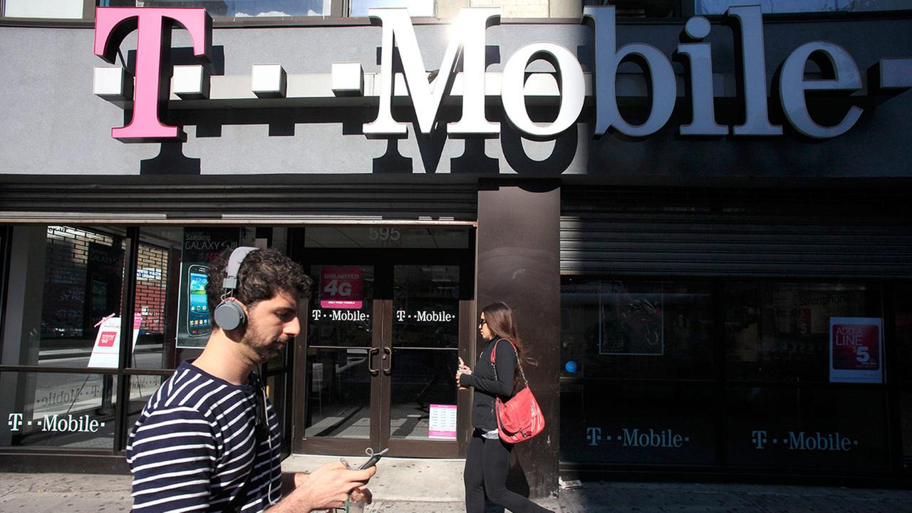 FILE - This Sept. 12, 2012 file photo shows a man using a cellphone as he passes a T-Mobile store in New York.