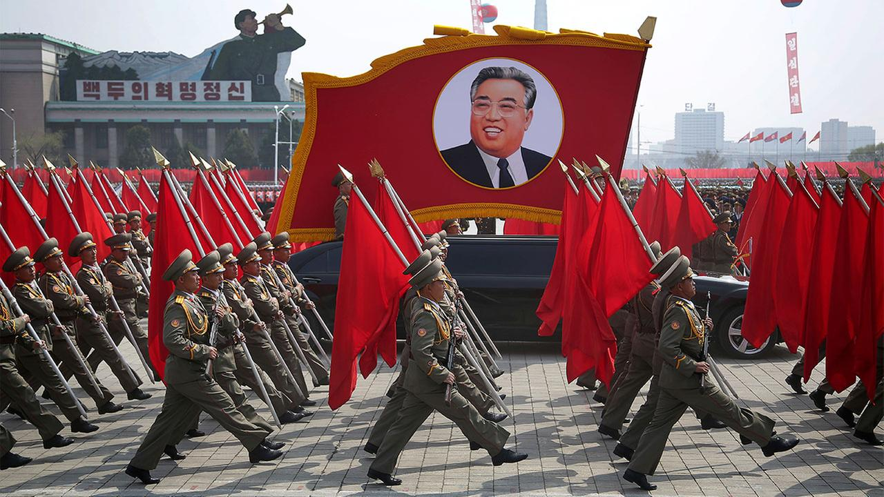 North Korean soldiers carry flags and a photo of late leader Kim Il Sung as they march across Kim Il Sung Square during a military parade on Saturday, April 15, 2017, in Pyongyang