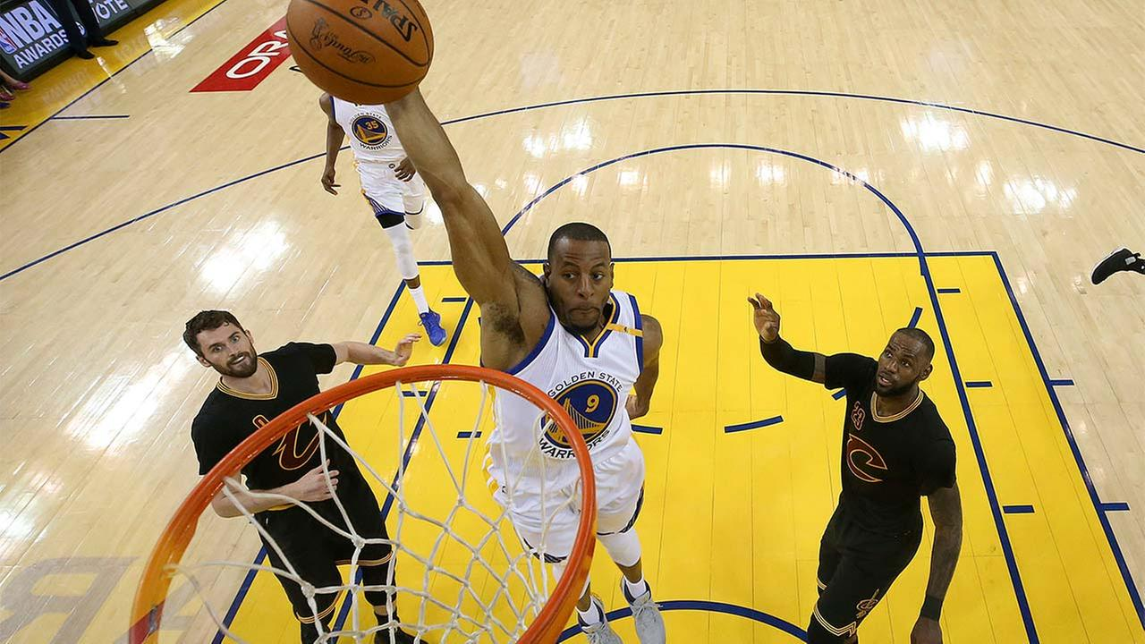 Golden State Warriors forward Andre Iguodala (9) dunks between Cleveland Cavaliers forward Kevin Love (0) and forward LeBron James (23) during the first half of Game 5.